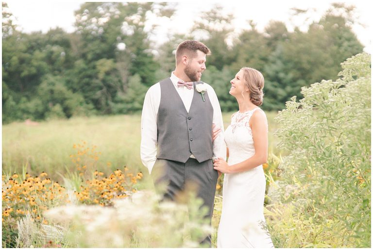 bride and groom in a field of wildflowers